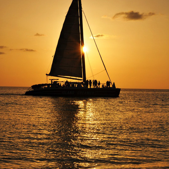 """A boat in the sea passing the sunset in Jamaica"" stock image"