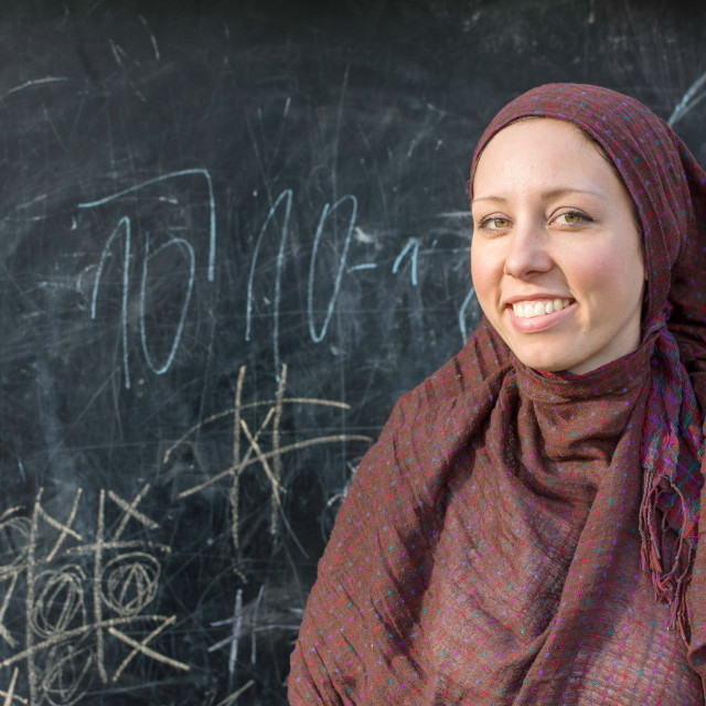 """Happy teacher in hijab in front of the blackboard"" stock image"