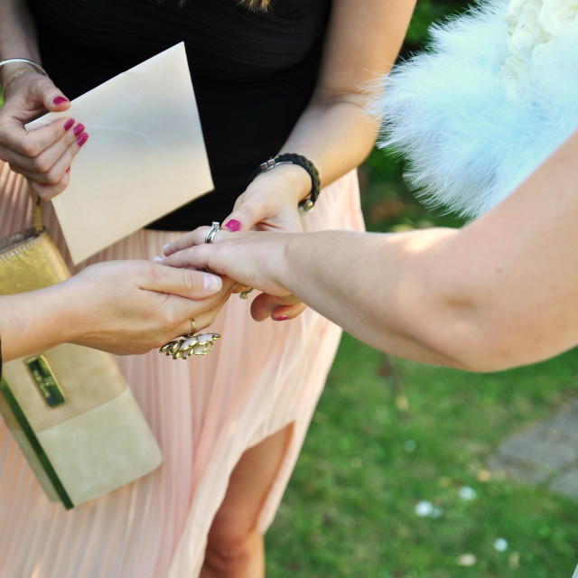 """Bride shows her new wedding ring to female friends"" stock image"