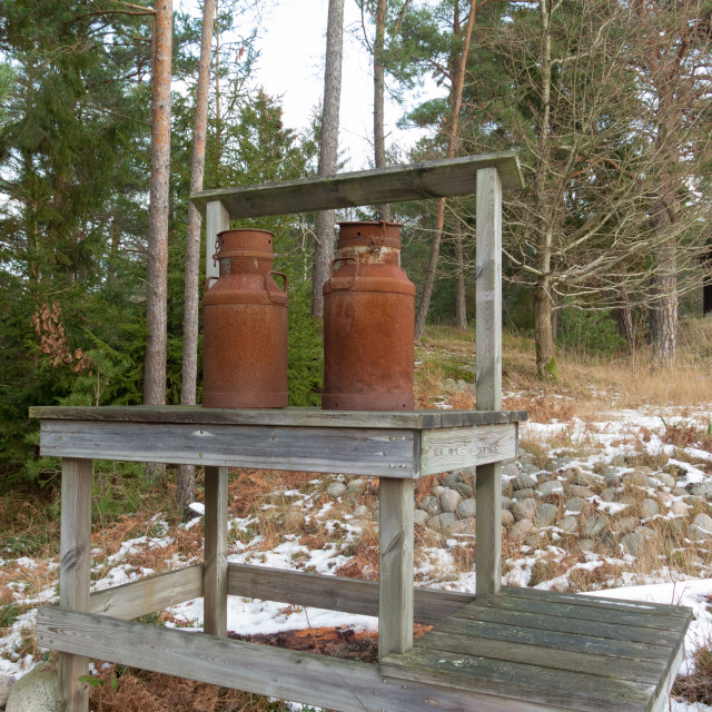 """""""two old rusty milk jug on a bench"""" stock image"""