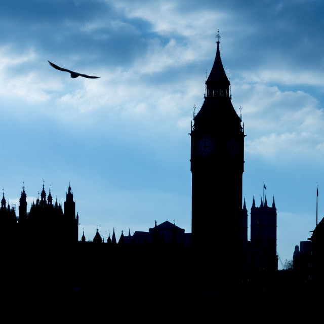 """Silhouette of the Houses of Parliament against a blue overcast sky"" stock image"