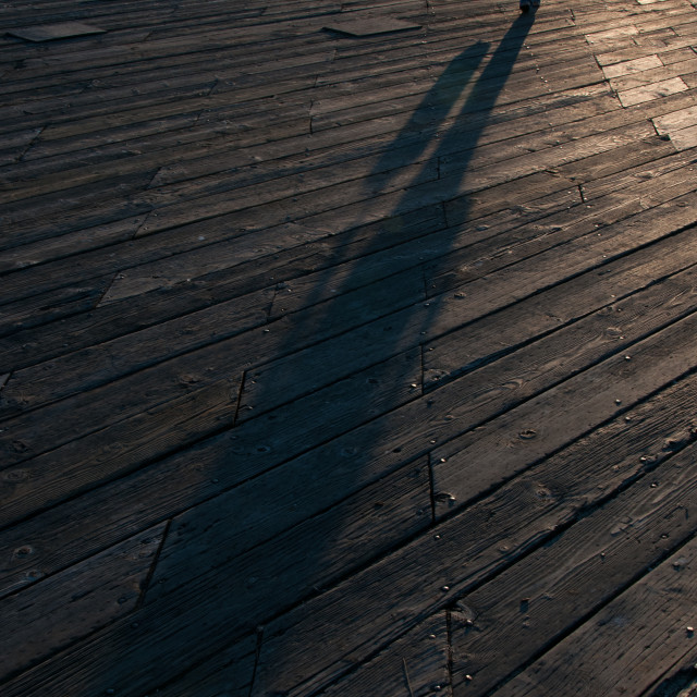 """Long shadow across pier"" stock image"