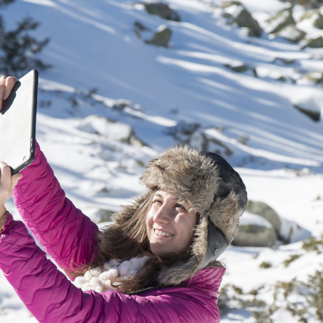 """Young girl makes selfie photos with a tablet in winter"" stock image"