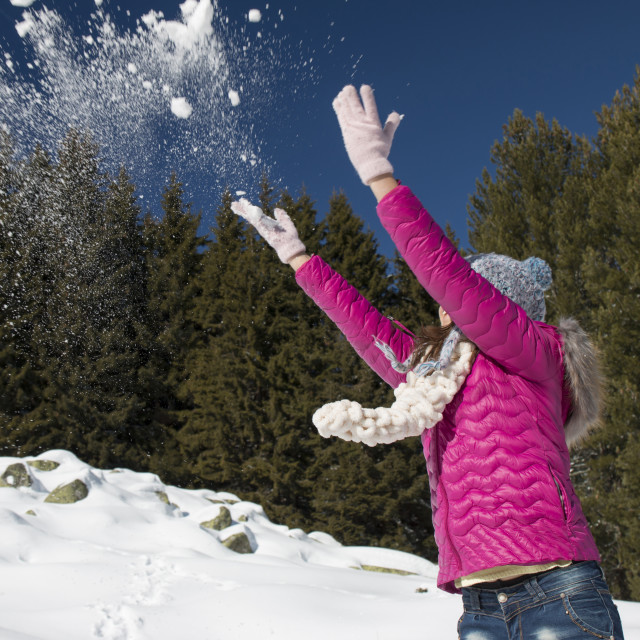 """A young girl plays with snow in winter"" stock image"