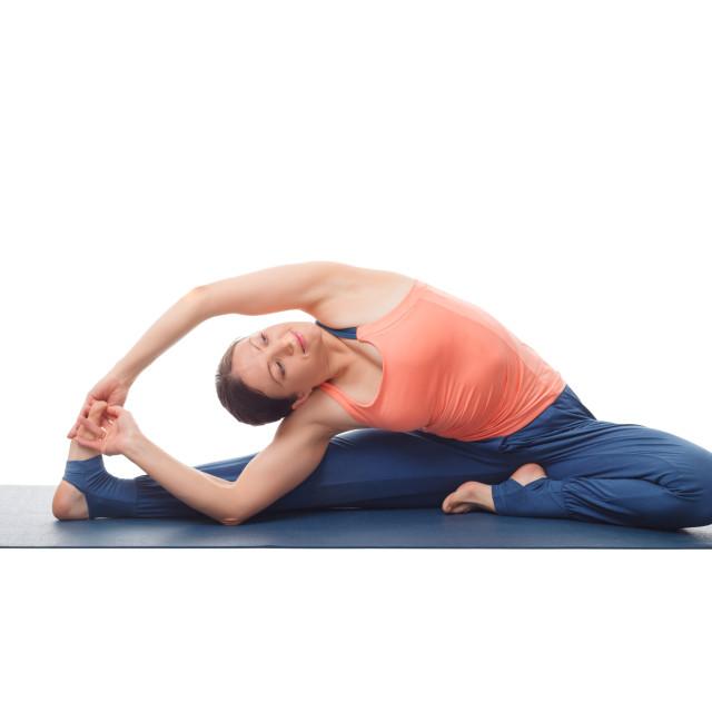 """Woman doing yoga asana parivrtta janu sirshasana"" stock image"