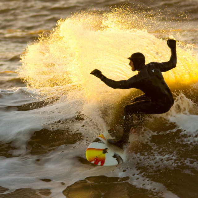 """""""A surfer at sunset enjoys riding the waves."""" stock image"""