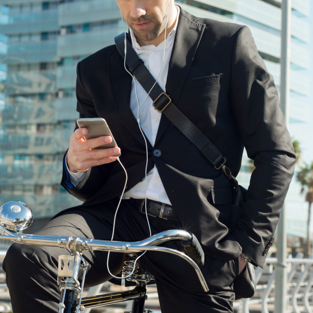 """Businessman in bicycle listens to earphones of the telephone"" stock image"