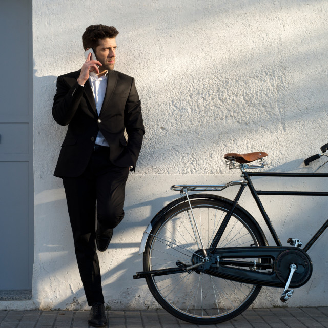"""businessman with bicycle listens to telephone supported in the w"" stock image"