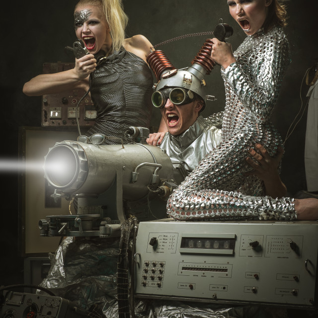 """""""Two girls and a man firing a weapon of the future."""" stock image"""