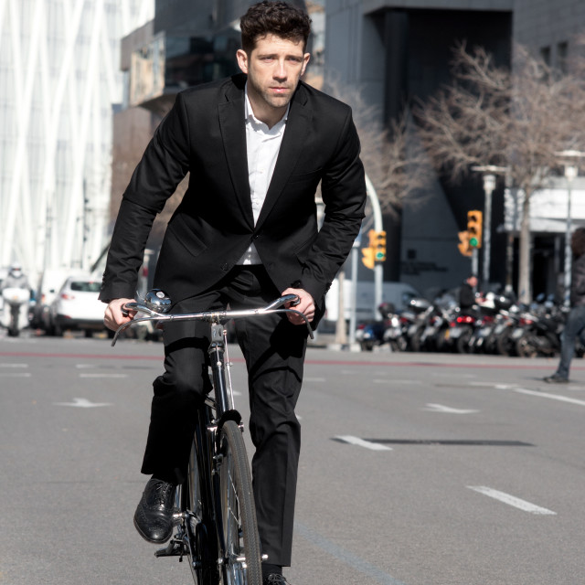 """Man cycling around town"" stock image"