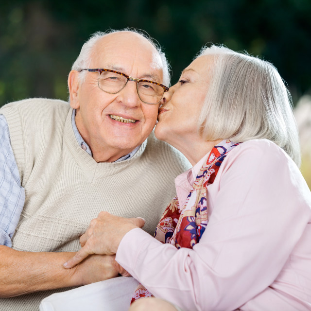 """Senior Woman Kissing On Man's Cheek"" stock image"