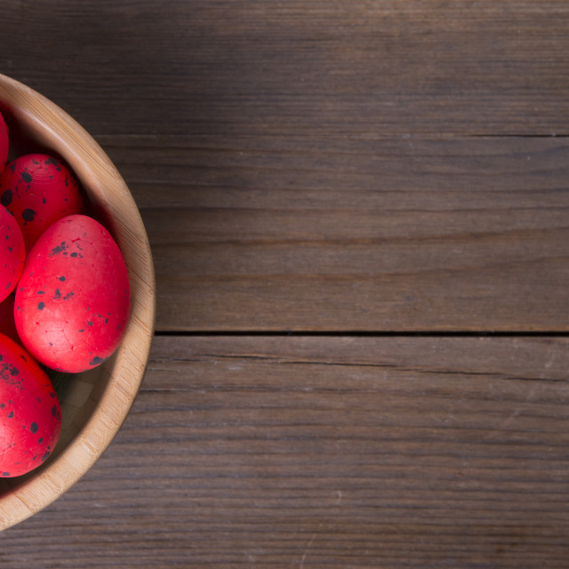 """Red Easter eggs on wooden bowl"" stock image"