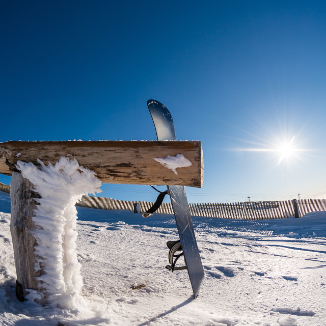 """""""Snowboard leaning on a wood rail"""" stock image"""