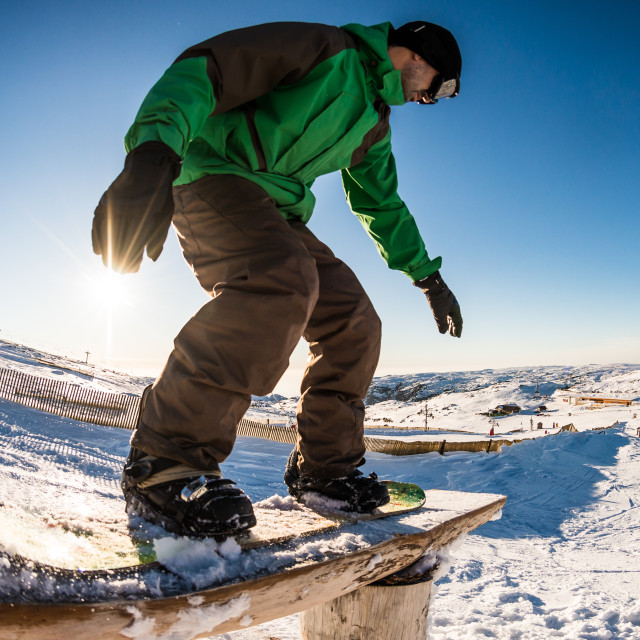 """Snowboarder sliding on a rail"" stock image"
