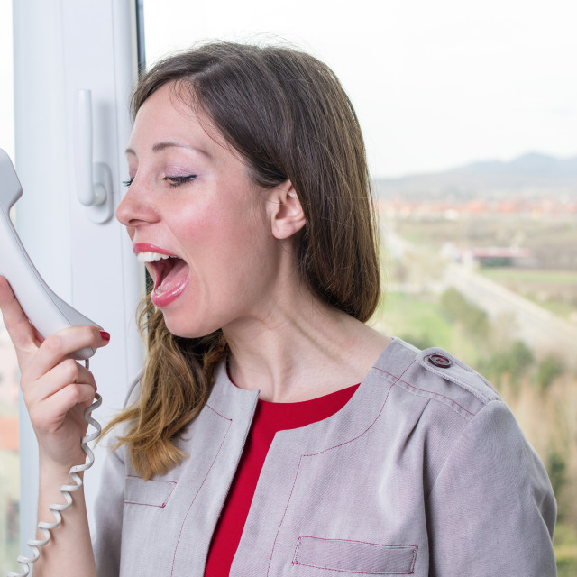 """""""Young businesswoman yelling at the phone"""" stock image"""