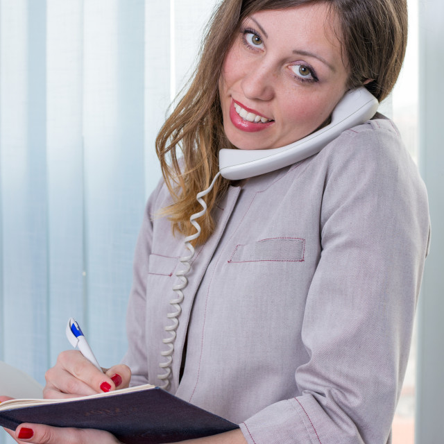 """""""Young businesswoman with notebook on the phone"""" stock image"""