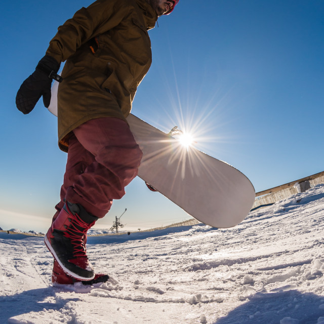 """Snowboarder walking against blue sky"" stock image"