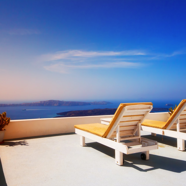 """Lounge chairs overlooking the Santorini caldera, Imerovigli village, Greece"" stock image"