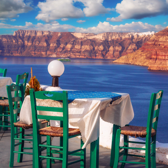"""""""Traditional Greek restaurant with a view of the Santorini caldera at sunset"""" stock image"""