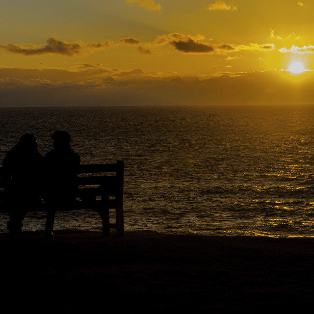 """A couple take in the sunset on the headland looking over Cardigan Bay"" stock image"