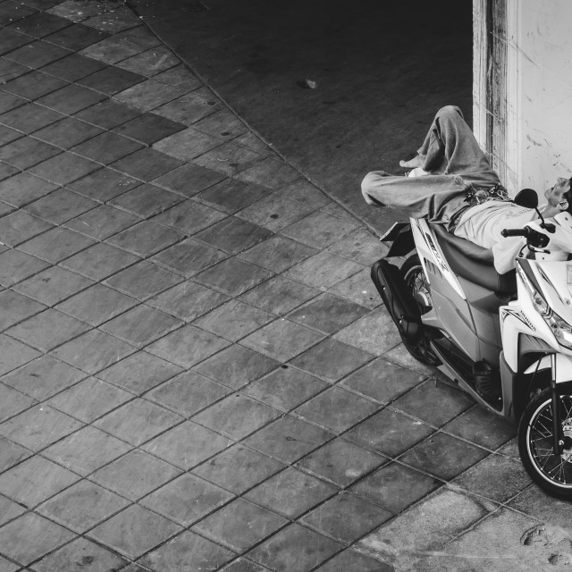 """Man sleeping on scooter"" stock image"