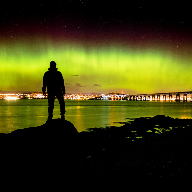 """Silhouette of figure watching aurora borealis over Dundee, Scotland"" stock image"