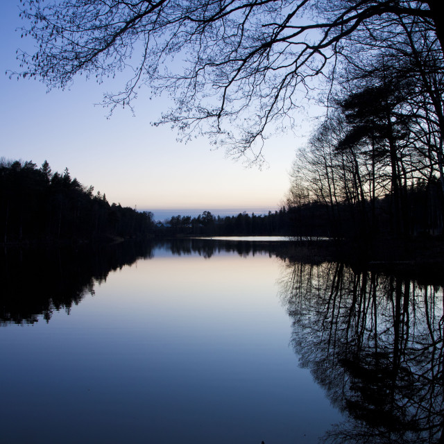 """""""Sweden. Small lake at dusk with trees reflection"""" stock image"""