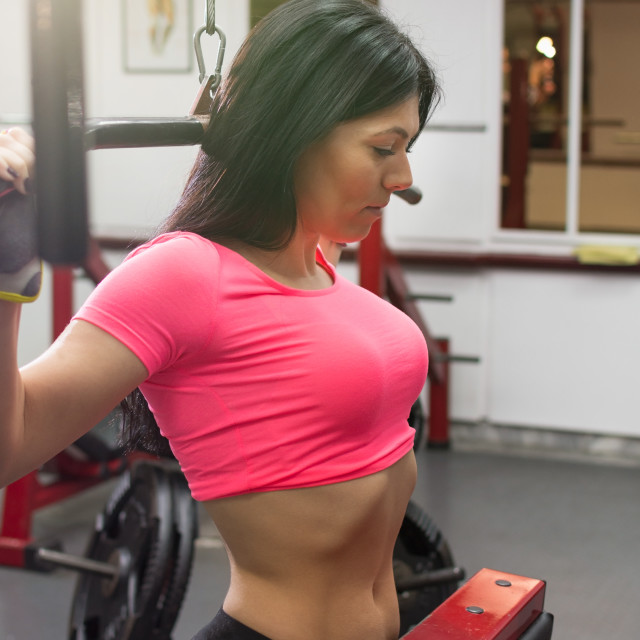 """""""Brunette working out on the lat machine"""" stock image"""