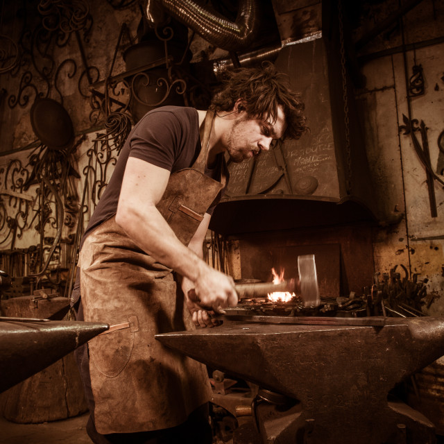 """Ironworker forging hot iron in workshop"" stock image"