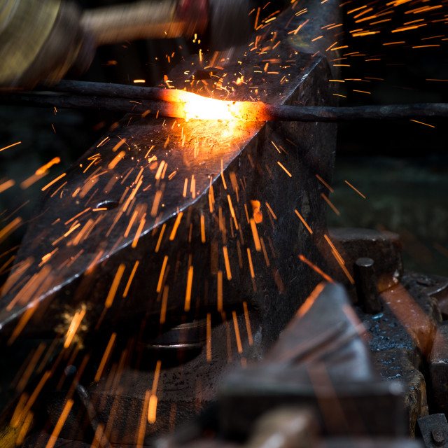 """Blacksmith shaping a hot piece of iron on an anvil with a hammer"" stock image"