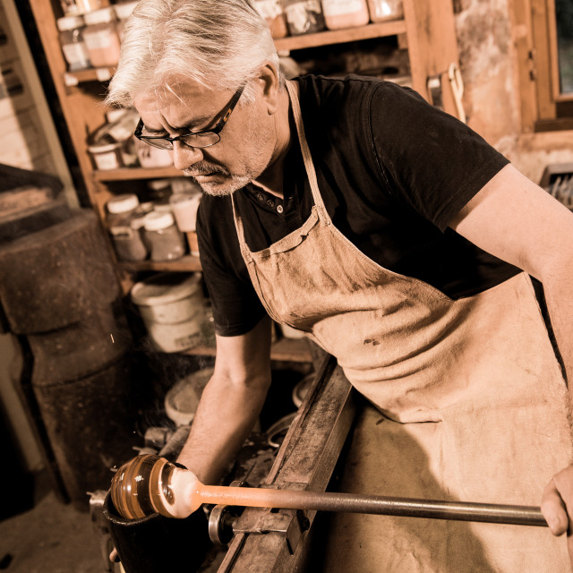 """""""Glassblower forming molten glass in his worshop"""" stock image"""