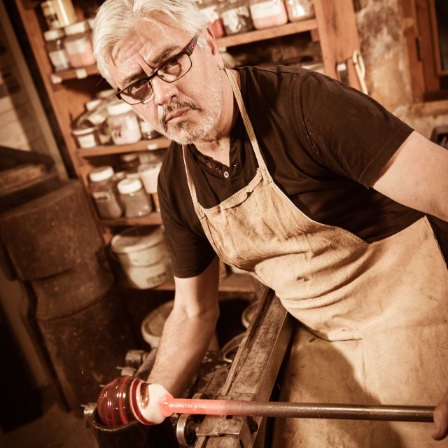 """Glassblower forming molten glass in his worshop"" stock image"