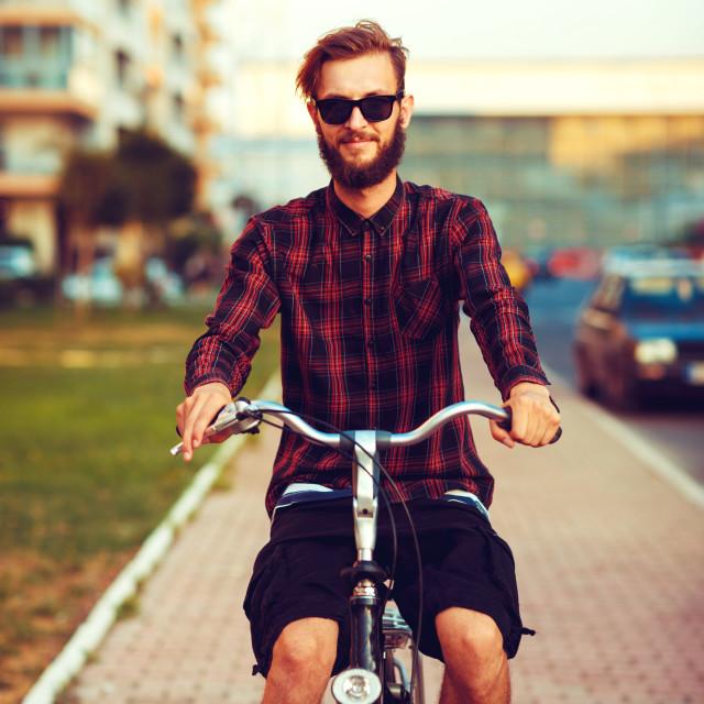"""Stylish man in sunglasses riding a bike on city street"" stock image"