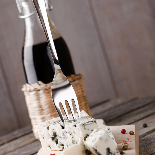 """""""Fork in blue cheese placed on wooden board"""" stock image"""