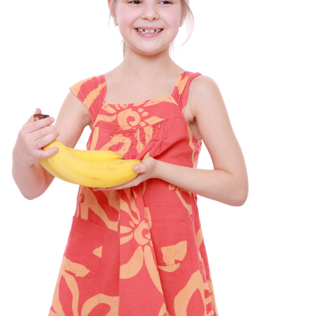 """Happy cheerful little girl holding yellow bananas/Happy girl holds a bunch of..."" stock image"