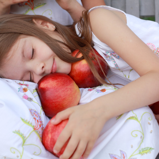 """Young girl outdoors in a white dress holding red apples"" stock image"