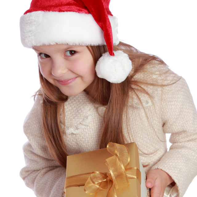 """""""Studio portrait of a happy surprised little girl with long hair in red Santa..."""" stock image"""