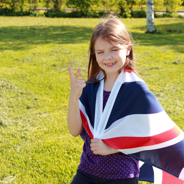 """""""Caucasian cheerful cute girl standing in a park holding a big Britain flag..."""" stock image"""