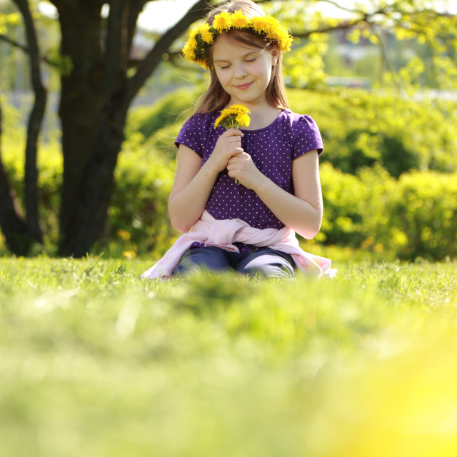 """Sweet little girl with floral head wreath at the spring park, moscow, russia"" stock image"