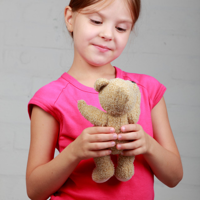 """""""Portrait of an adorable toddler girl hugging a teddy bear"""" stock image"""