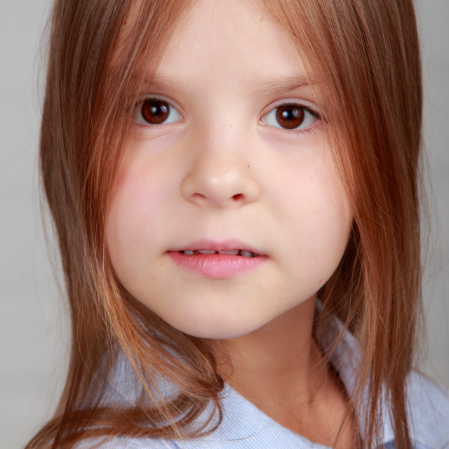"""""""Portrait of a emotional beautiful little girl on gray background"""" stock image"""