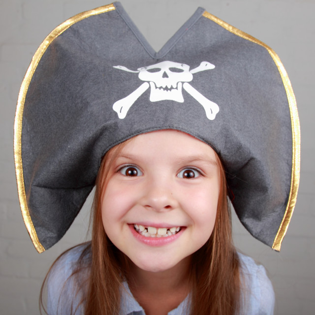 """""""Portrait of a cute cheerful little girl in a pirate hat hamming and makes a..."""" stock image"""