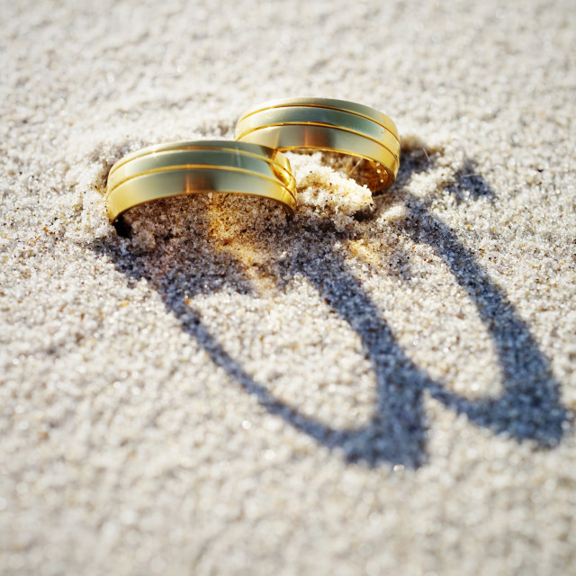 """""""Wedding rings at the beach with shadow"""" stock image"""