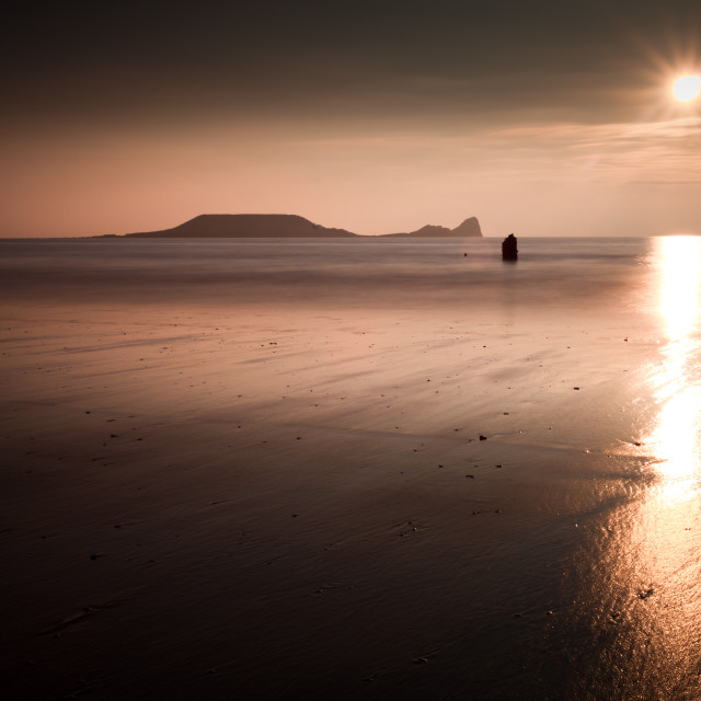 """Sunset and wet sand at Worms Head, Gower, Wales"" stock image"