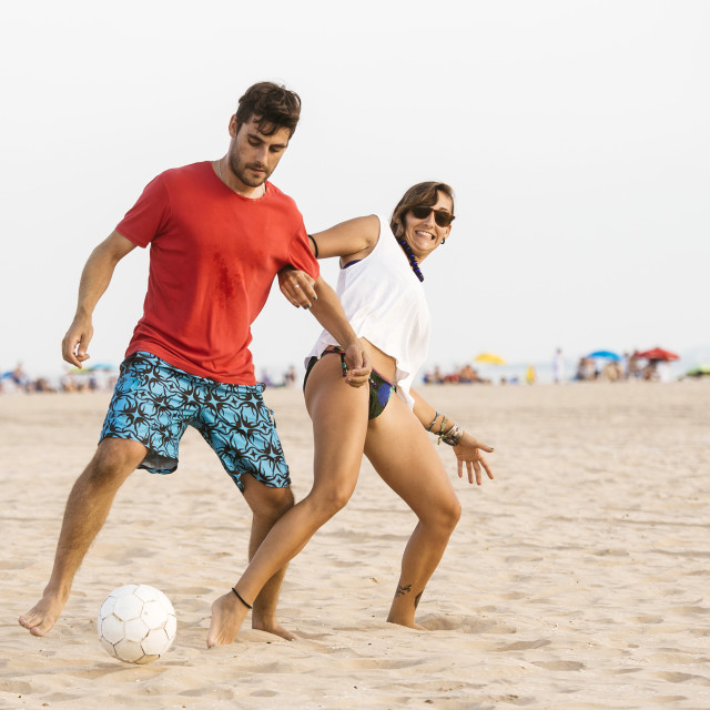 """Young couple playing football on the beach"" stock image"