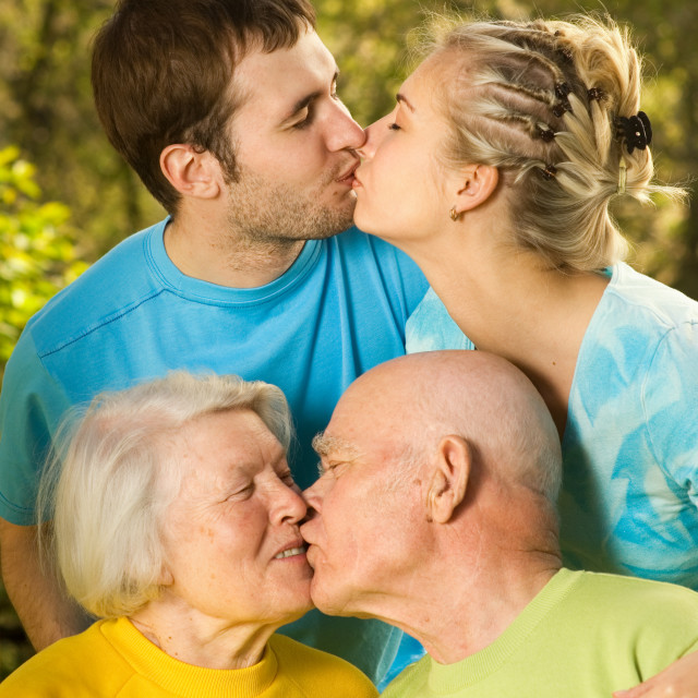 """""""Young and senior couples kissing outdoors"""" stock image"""