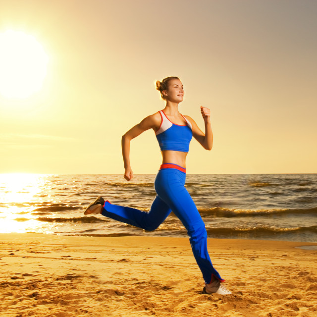 """""""Beautiful young woman running on a beach at sunset (real shot, background is..."""" stock image"""