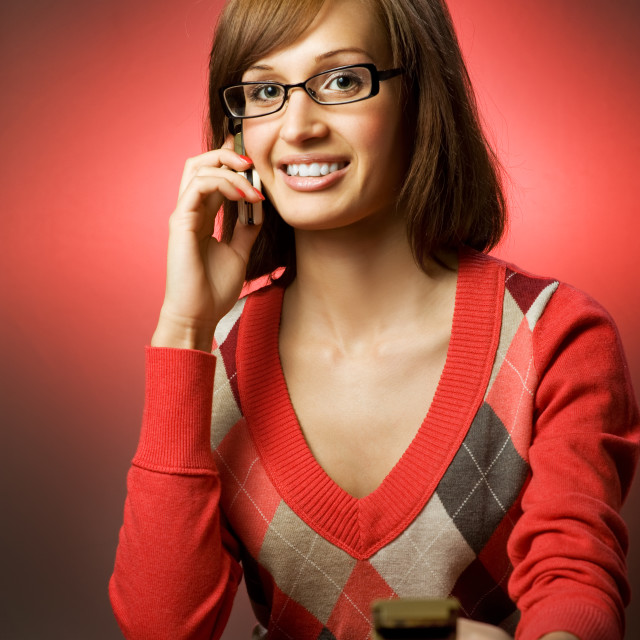 """""""Beautiful redhead woman searching a phone number in telephone directory"""" stock image"""