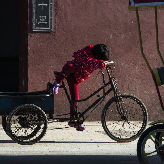 """A little girl playing with a tricycle, China"" stock image"