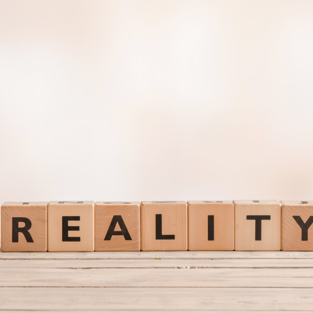 """Reality sign on a table of wood"" stock image"